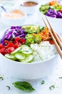 Tazones de sushi veganos hechos con arroz de sushi perfecto, pepinos, pimientos, aguacate, zanahorias y repollo.
