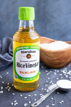 Una botella de vinagre de arroz y azúcar como ingredientes para sazonar el arroz de sushi.