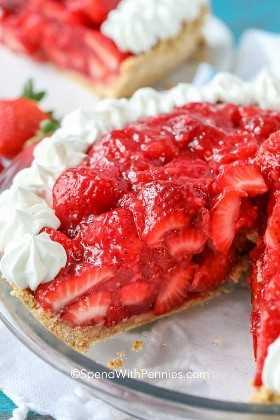 Un pastel de fresas sin hornear en un molde para pastel con una rebanada eliminada.