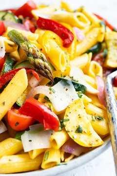 Espárragos asados, calabacín, calabacín amarillo y pimientos con pasta penne vegana y sin gluten.