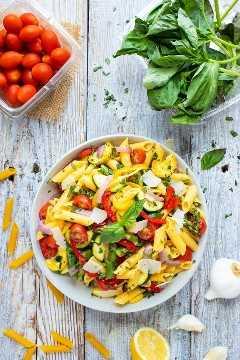 Una pinta de tomates, albahaca fresca y un bol lleno de pasta de primavera.