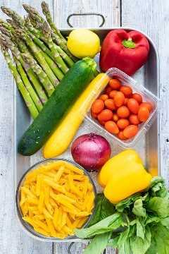 Espárragos, pimientos, tomates, pastas, calabazas, albahaca y limón como ingredientes para una receta de pasta de primavera con salsa de ajo y mantequilla de limón.
