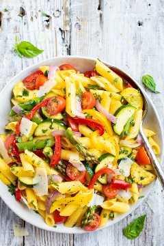 Un gran tazón blanco lleno de una pasta vegetal asada fácil y saludable con tomates, espárragos y pimientos.