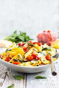 Un plato de servir lleno de una receta de pasta de primavera con una cuchara de plata.