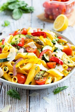 Un tazón lleno de una receta de pasta de primavera con salsa de ajo mantequilla de limón con albahaca y tomates.