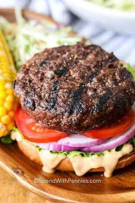 Una hamburguesa de ternera clásica ensamblada con tomates, cebollas rojas, lechuga y salsa.