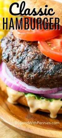 Una hamburguesa en un bollo con tomate, lechuga, cebolla roja y salsa.