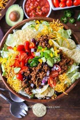 Una vista superior de una ensalada de taco en un tazón marrón con ingredientes como salsa, aguacate, tomates y jalapeños cortados en un lado.