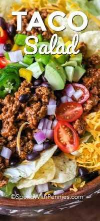 Ensalada de tacos llena de carne molida, frijoles, chips de tortilla y queso, junto con ingredientes frescos como el aguacate, los tomates, la cebolla roja y los jalapeños cortados en cubitos.