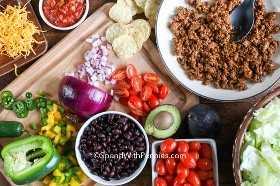 Todos los ingredientes para hacer una ensalada de tacos montados en una tabla de madera.