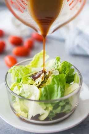 Lloviznando aderezo de vinagre balsámico sobre ensaladas verdes.