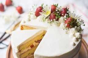 Torta de cumpleaños de la torta de frutas de la fresa adornada con las flores frescas y las fresas.