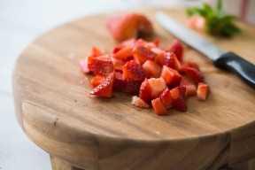Fresas aproximadamente picadas en una tabla de cortar de madera.