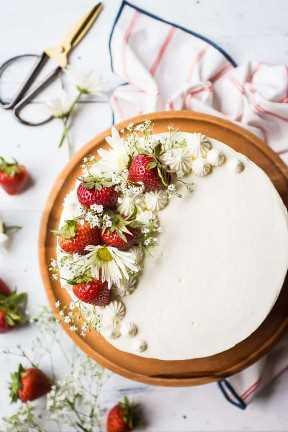 Imagen de arriba de una torta de la torta de frutas de la fresa con las fresas y las flores frescas, en un soporte de madera de la torta.