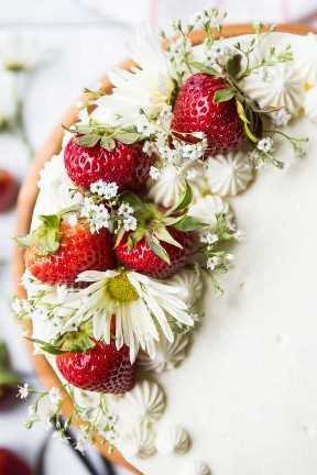 Imagen del primer de fresas y de flores frescas en la torta de la torta de frutas de la fresa.
