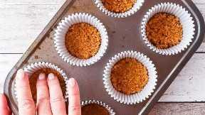Pressionando a massa de biscoito de graham nos poços de uma bandeja para cupcakes.
