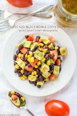 Ensalada de aguacate de maíz con frijoles negros y vinagreta de limón en un tazón blanco