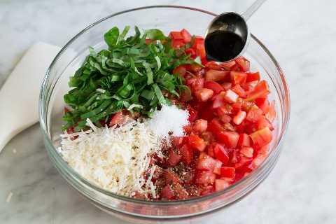 Bruschetta ingredientes en un tazón de vidrio antes de mezclar