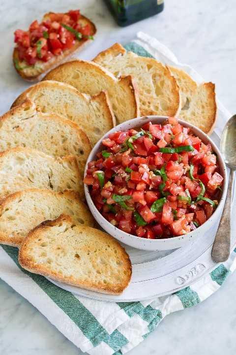Bruschetta de tomate rematado en un tazón de servir blanco con pan francés tostado a un lado