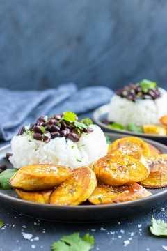 Dois pratos cinza com banana frita, arroz branco e feijão.