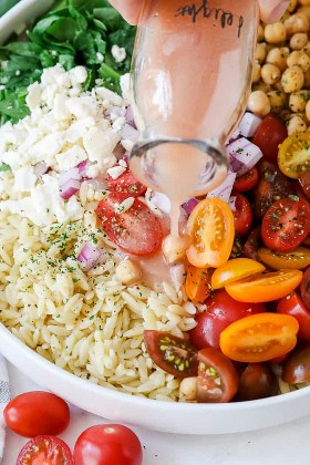 Ciérrese para arriba de los ingredientes de la ensalada de pasta del orzo en un cuenco con la preparación que es vertida sobre tapa.