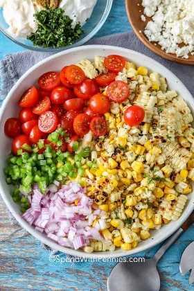 Un tazón lleno de ingredientes de ensalada de maíz mexicano.