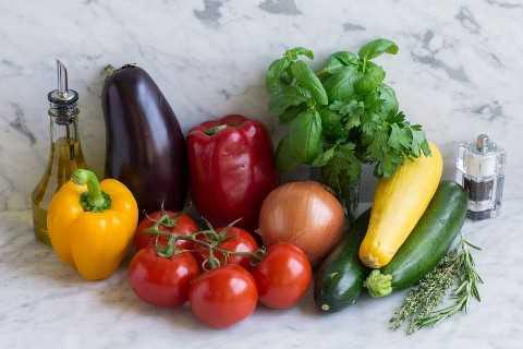 Los ingredientes de ratatouille que se muestran aquí incluyen aceite de oliva, pimientos, tomates, cebolla, albahaca, perejil, tomillo, romero, calabaza, calabacín, sal y pimienta.