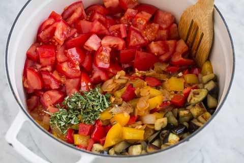 Agregue los tomates, la mezcla de pimientos, la berenjena y las hierbas frescas a la olla para hacer ratatouille.