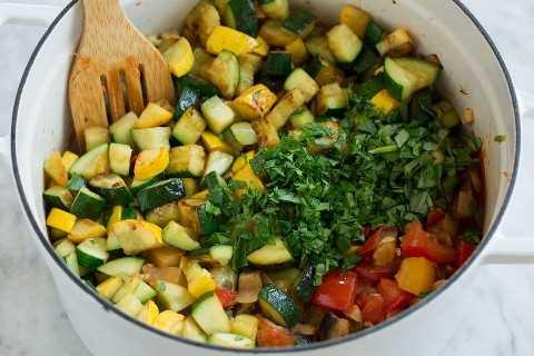 Agregando calabaza y más hierbas frescas a la mezcla de pisto.