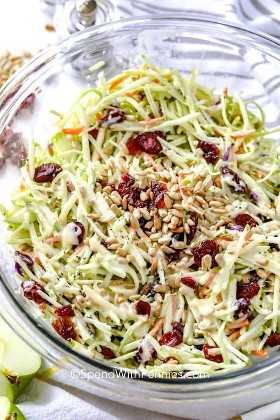 Ensalada de col brócoli mezclada en un tazón y rematada con arándanos y semillas de girasol.