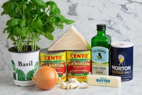 Los ingredientes necesarios para hacer la salsa marinara que se muestran aquí incluyen tomates enlatados de San Marzano, aceite de oliva virgen extra, ajo, mantequilla, parmesano, albahaca, cebolla y sal.