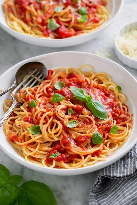 Salsa marinara servida con espagueti, parmesano y albahaca fresca. Se muestra en un tazón de pasta blanca.