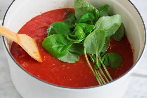 Agregar tomates machacados y albahaca fresca a la olla.