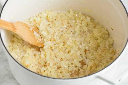 Saltear la cebolla y el ajo en una olla grande y blanca.
