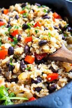 Frijoles negros, arroz, pimientos rojos y cilantro en una sartén negra.