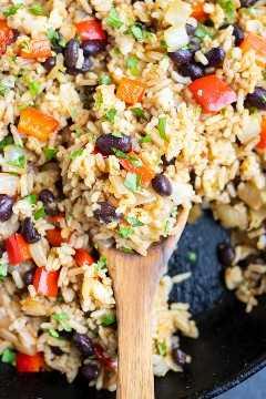 Una cuchara de madera sacando una porción de una receta costarricense de frijoles y arroz.