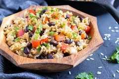 Un tazón de madera lleno de una receta fácil de gallo pinto que es el plato tradicional costarricense.