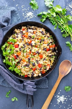 Una auténtica receta costarricense de Gallo Pinto en una sartén junto a una cuchara de madera, cilantro y arroz.