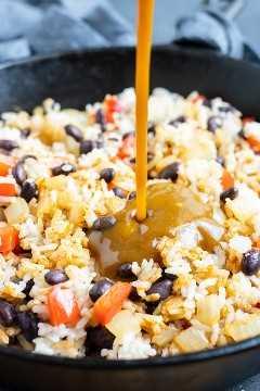 Salsa Lizano se vierte en una sartén llena de arroz y frijoles negros.