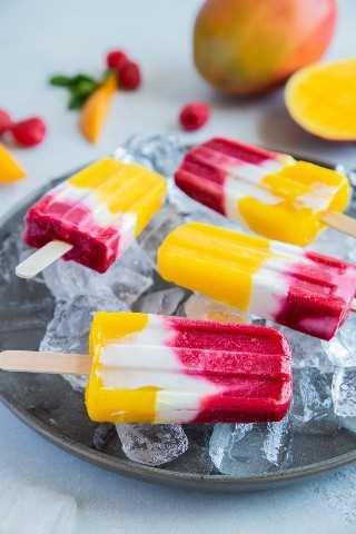 Paletas de yogur de frambuesa y mango en una placa gris sobre hielo.
