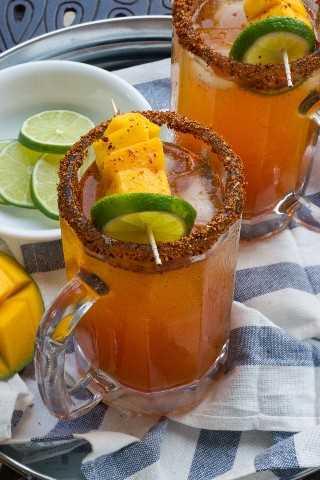 Un cóctel dulce y picante hecho con jugo de vegetales, tequila de mango, Tajin, salsa picante y cerveza. ¡Esta picante Michelada de mango es la bebida perfecta junto a la piscina este verano! #RedHotSummer #ad #IPSTOE
