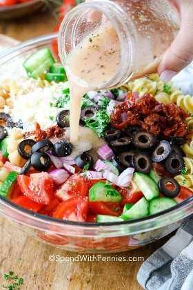 Ensalada de pasta mediterránea con aderezo se vierte en la parte superior.