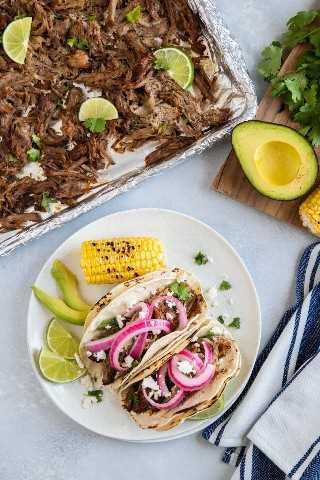 Carnitas de cerdo en una bandeja para hornear y un plato con dos tacos de carnitas servidos con cebolla en escabeche, aguacate y maíz.