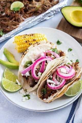 Tacos de carnitas de cerdo con cebolla en escabeche y rodajas de lima, aguacate y maíz a un lado.