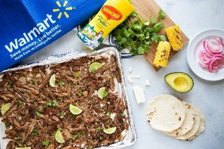 Bandeja de horno con carnitas de cerdo y tortillas, aguacate, cebolla en escabeche, maíz a la parrilla y queso fresco a un lado.