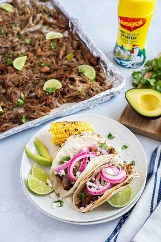 Tacos de carnitas de cerdo con cebolla en escabeche y queso fresco y servidos con rodajas de lima, aguacate y maíz a la parrilla.