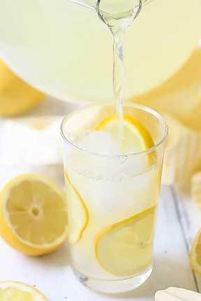 Verter limonada de una jarra de vidrio en un vaso alto de hielo con rodajas de limón.