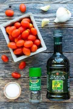 Tomates cherry y uvas, aceite de oliva, pimienta negra molida, sal marina y ajo como ingredientes para una receta de tomates asados.