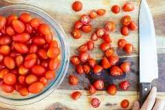 Tomates cherry se cortan por la mitad en una tabla para cortar madera.