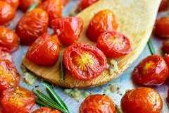 Tomates asados en una bandeja para hornear de plata con ajo y romero.
